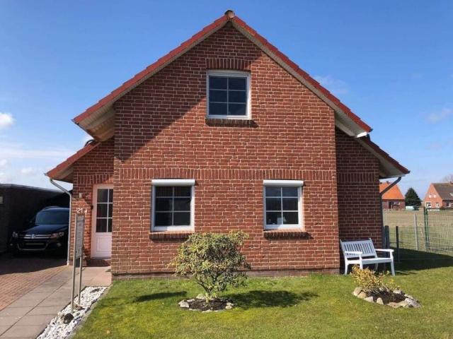 Hausfassade Ferienhaus Roese mit Garten und weißer Bank