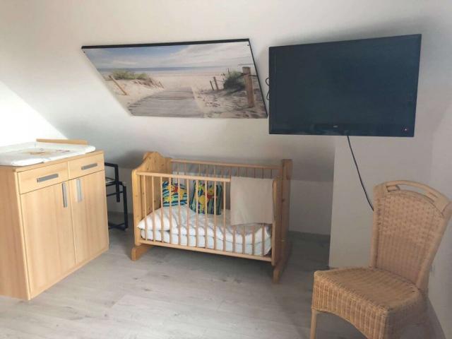 Schlafzimmer mit Babybett und Wickeltisch