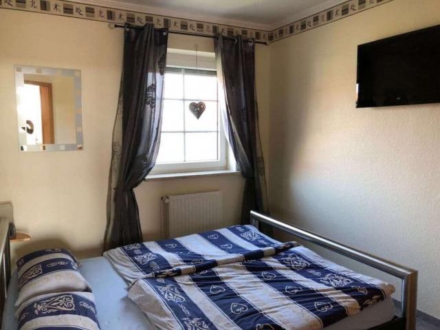 Ebenerdiges Schlafzimmer mit Doppelbett und TV