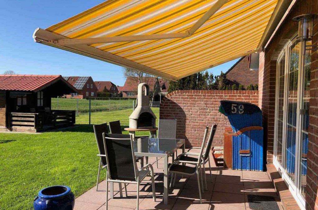 Terrasse mit Markise und Gartenmöbeln und Strandkorb