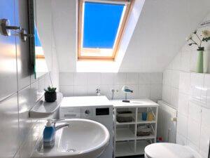 weiß gefliestes Badezimmer mit Waschbecken, Waschmaschine und WC