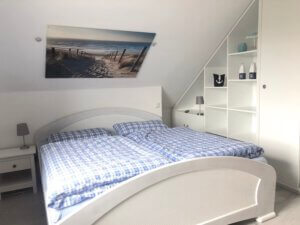 Schlafzimmer mit weißem Doppelbett und Einbauschrank