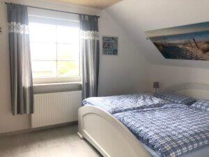 Schlafzimmer mit weißem Doppelbett und karierter Bettwäsche